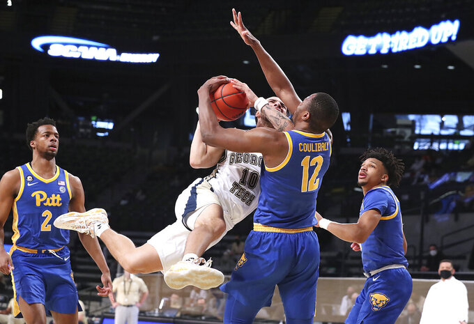 Georgia Tech guard Jose Alvarado is fouled by Pittsburgh forward Abdoul Karim Coulibaly (12) while driving to the basket during an NCAA college basketball game on Sunday, Feb. 14, 2021, in Atlanta. (Curtis Compton/Atlanta Journal-Constitution via AP)