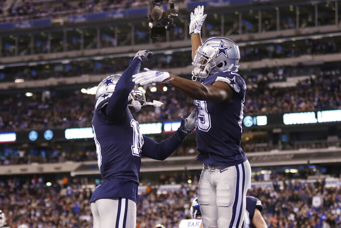 Dallas Cowboys wide receiver Michael Gallup (13) celebrates with wide receiver Amari Cooper (19) after scoring a touchdown during the fourth quarter of an NFL football game against the New York Giants, Monday, Nov. 4, 2019, in East Rutherford, N.J. (AP Photo/Adam Hunger)