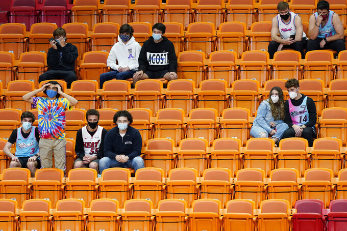 Fans watch during the second half of an NBA basketball game between the Miami Heat and the Los Angeles Clippers, Thursday, Jan. 28, 2021, in Miami. The Miami Heat allowed a limited number of fans to attend the game. (AP Photo/Marta Lavandier)