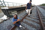 Brian Peets sits on the tracks during a visit from the outreach team including Peter Lagasse, right, at a homeless camp in New Bedford, Mass., on Friday, Aug. 10, 2018. Lagasse is part of a team of clergy from a variety of faiths who regularly crisscross town with police officers and counselors. Their goal is to get them into treatment and, if they will listen, to offer some spiritual advice. (AP Photo/Michael Dwyer)