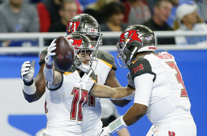 Tampa Bay Buccaneers wide receiver Scott Miller (10) is hugged by quarterback Jameis Winston (3) after Miller's 33-yard reception for a touchdown during the first half of an NFL football game against the Detroit Lions, Sunday, Dec. 15, 2019, in Detroit. (AP Photo/Duane Burleson)