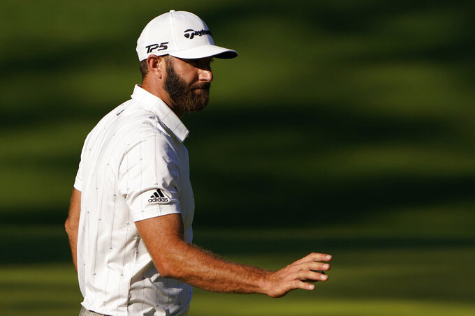 Dustin Johnson waves after putting on the 10th hole during the third round of the Masters golf tournament Saturday, Nov. 14, 2020, in Augusta, Ga. (AP Photo/Chris Carlson)