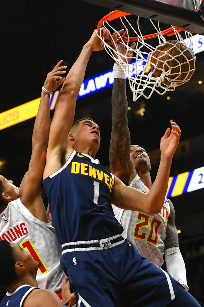 Denver Nuggets forward Michael Porter Jr. (1) dunks as Atlanta Hawks forward John Collins (20) and guard Trae Young defend during the second half of an NBA basketball game Monday, Jan. 6, 2020, in Atlanta. (AP Photo/John Amis)