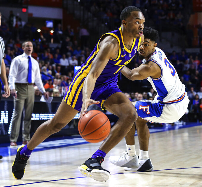 LSU guard Javonte Smart (1) drives to the basket while defended by Florida guard Jalen Hudson (3) during the first half of an NCAA college basketball game in Gainesville, Fla., Wednesday, March 6, 2019. (AP Photo/Gary McCullough)