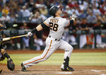 FILE - In this Friday, May 17, 2019, file photo, San Francisco Giants' Buster Posey watches the flight of his fly ball against the Arizona Diamondbacks during the third inning of a baseball game, in Phoenix. Posey is the latest big-name player to skip this season because of concerns over the coronavirus pandemic. Posey announced his decision on Friday, July 10, 2020. He says his family finalized the adoption of identical twin girls this week. The babies were born prematurely and Posey said after consultations with his wife and doctor he decided to opt out of the season.(AP Photo/Ralph Freso, File)