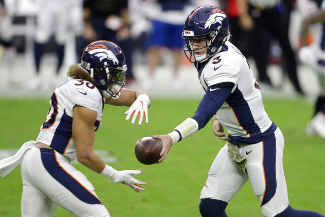 Denver Broncos quarterback Drew Lock (3) hands the ball off to running back Phillip Lindsay (30) during the first half of an NFL football game against the Las Vegas Raiders, Sunday, Nov. 15, 2020, in Las Vegas. (AP Photo/Isaac Brekken)