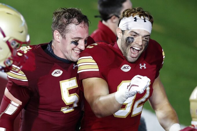 Boston College quarterback Phil Jurkovec (5) and linebacker Nick DeNucci (32) celebrate after the team's win over Texas State in an NCAA college football game Saturday, Sept. 26, 2020, in Boston. (AP Photo/Michael Dwyer)