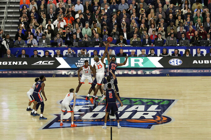 Virginia's Mamadi Diakite (25) and Auburn's Anfernee McLemore (24) reach for the tipoff at the start of the first half in the semifinals of the Final Four NCAA college basketball tournament, Saturday, April 6, 2019, in Minneapolis. (AP Photo/Matt York)