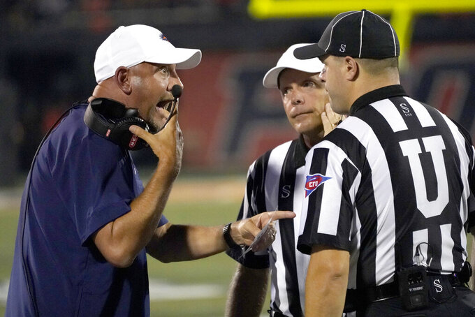 UTSA head coach Jeff Taylor, left, talks with the officials during the first half of an NCAA college football game against Illinois, Saturday, Sept. 4, 2021, in Champaign, Ill. (AP Photo/Charles Rex Arbogast)