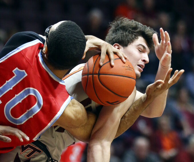 Hunter Cattoor (0) of Virginia Tech and Ronald Lucas (10) of Delaware State wrestle for a rebound in the first half of an NCAA college basketball game in Blacksburg Va. Wednesday, Nov. 20 2019. (Matt Gentry/The Roanoke Times via AP)