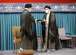 In this photo released by an official website of the office of the Iranian supreme leader, newly elected President Ebrahim Raisi, right, receives the official seal of approval from Supreme Leader Ayatollah Ali Khamenei in an endorsement ceremony in Tehran, Iran, Tuesday, Aug. 3, 2021. (Office of the Iranian Supreme Leader via AP)