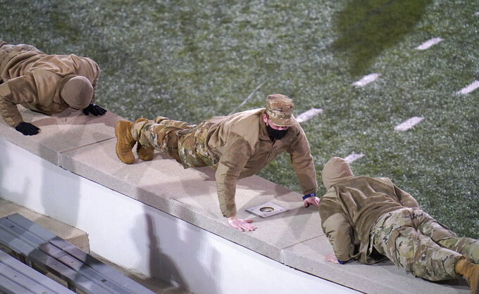 Cadets do pushups after a touchdown by Air Force in the second half of an NCAA college football game against Boise State, Saturday Oct. 31 2020, at Air Force Academy, Colo. (AP Photo/David Zalubowski)