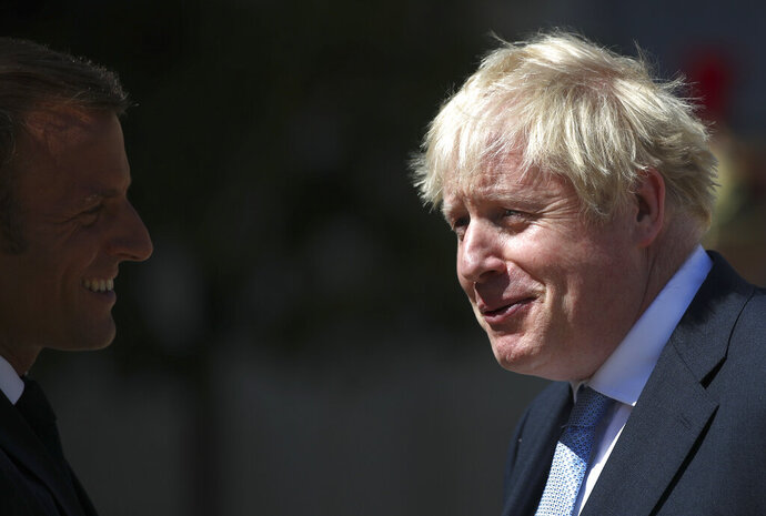 French President Emmanuel Macron welcomes Britain's Prime Minister Boris Johnson at the Elysee Palace, Thursday, Aug. 22, 2019 in Paris. Welcoming British Prime Minister Boris Johnson to the courtyard of his Elysee Palace Thursday with a big smile and little pats on the back, Macron remained firm on his position that renegotiating the deal for Britain to leave the European Union is not an option. (AP Photo/Daniel Cole)