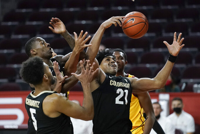 Colorado's Evan Battey, center, grabs a rebound during the second half of the team's NCAA college basketball game against Southern California, Thursday, Dec. 31, 2020, in Los Angeles. Colorado won 72-62. (AP Photo/Jae C. Hong)