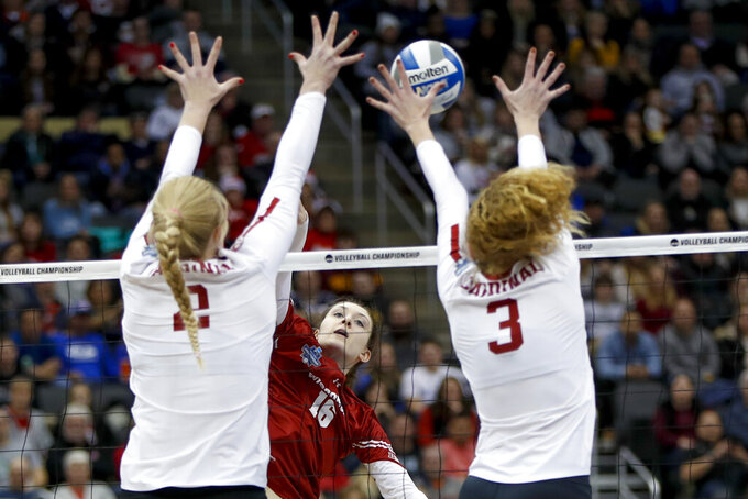 FILE - In this Dec. 21, 2019, file photo, Wisconsin's Dana Rettke (16) has a spike blocked by Stanford's Holly Campbell (3) and Kate Formico (11) during the NCAA Division I women's volleyball championship match in Pittsburgh. Athletes in sports other than football say they were not surprised to see the Big Ten and Pac-12 conferences postpone fall sports until the spring. Even though they will continue training, some wonder if it will be possible to play or whether the coronavirus will cancel their seasons as well. (AP Photo/Keith Srakocic, File)
