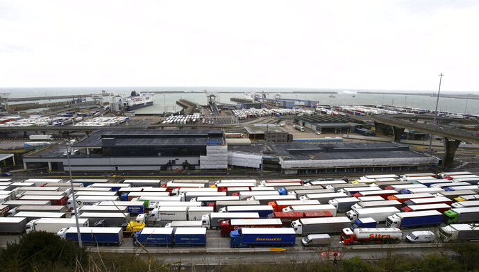 FILE - In this Tuesday March 12, 2019 file photo, lorries queue at the entrance to the Port of Dover ferry terminal during delays to the cross Channel ferry, in Dover, England. Britain unveiled a temporary tariff regime on Wednesday, March 13 that could boost the price of imports ranging from cars to butter if the U.K. leaves the European Union without an agreement on future trade, triggering fury among business leaders who weren't consulted on the proposals. The tariffs, which would last for up to 12 months, were published hours before lawmakers are scheduled to vote on whether to prevent the country from leaving the EU without a deal. (Gareth Fuller/PA via AP, file)