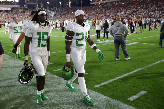 Oregon safety Jamal Hill (19) and linebacker Ge'mon Eaford leave the field after the team's NCAA college football game against Arizona State, Saturday, Nov. 23, 2019, in Tempe, Ariz. Arizona State won 31-28. (AP Photo/Matt York)