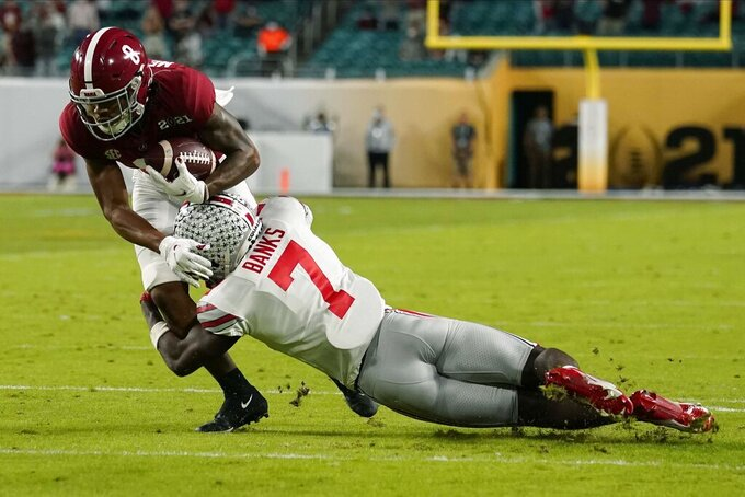 Alabama wide receiver John Metchie III is tackled by Ohio State cornerback Sevyn Banks during the first half of an NCAA College Football Playoff national championship game, Monday, Jan. 11, 2021, in Miami Gardens, Fla. (AP Photo/Lynne Sladky)
