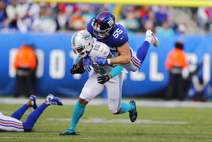 New York Giants outside linebacker David Mayo (55) tries to stop Miami Dolphins wide receiver Albert Wilson (15) during the first half of an NFL football game, Sunday, Dec. 15, 2019, in East Rutherford, N.J. (AP Photo/Adam Hunger)