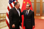 U.S. Secretary of State Mike Pompeo, left, chats with Chinese Foreign Minister Wang Yi before their meeting at the Great Hall of the People in Beijing, Thursday, June 14, 2018. (AP Photo/Andy Wong, Pool)