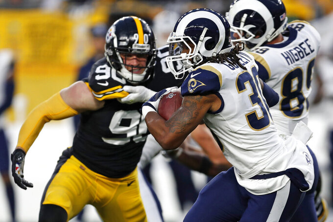 Los Angeles Rams running back Todd Gurley (30) carries the football under pressure from Pittsburgh Steelers outside linebacker T.J. Watt (90) during the first half of an NFL football game in Pittsburgh, Sunday, Nov. 10, 2019. (AP Photo/Keith Srakocic)