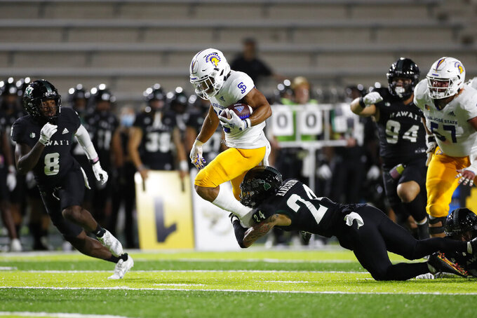 Hawaii defensive back Kai Kaneshiro (24) trips up San Jose State running back Kairee Robinson (32) during the first half of an NCAA college football game, Saturday, Sept. 18, 2021, in Honolulu. (AP Photo/Marco Garcia)