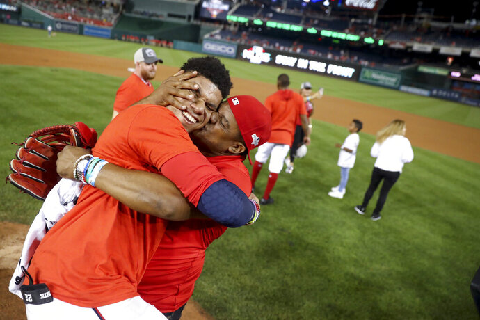 Washington Nationals' Juan Soto gets a kiss from his father, Juan Jose Soto, right, after defeating the Milwaukee Brewers 4-3 in a National League wild-card baseball game at Nationals Park, Tuesday, Oct. 1, 2019, in Washington. (AP Photo/Andrew Harnik)