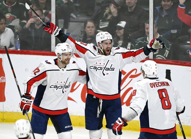 Washington Capitals' Evgeny Kuznetsov (92), of Russia, Tom Wilson (43) and Alex Ovechkin (8), of Russia, celebrate a goal by Wilson against the Minnesota Wild during the third period of an NHL hockey game, Sunday, March 1, 2020, in St. Paul, Minn. The Capitals won 4-3. (AP Photo/Hannah Foslien)
