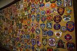 In this photo taken July 9, 2019, patches from a number of fire departments cover a board of the Joplin Fire Department in Joplin, Missouri. The fire department trains with scores of other fire departments around the country, which is invaluable when local first responders are overwhelmed by natural disasters. As police and firefighter numbers dwindle, authorities urge personal responsibility. (Brigette Waltermire/News21 via AP)