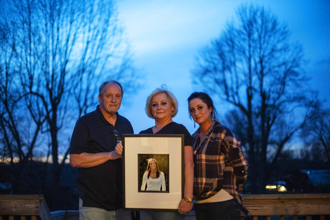 "Jeff and Lola Carter stand with their daughter, Amanda, and a framed photo of Kayla, their daughter who struggled with drug addiction, Tuesday, March 16, 2021, at their home in Milton, W.Va. Kayla was hospitalized in June with endocarditis, a heart infection common among injection drug users. It seemed like she was suddenly determined to live. In October, her mother couldn't reach her one Friday. She went to her apartment, and found her dead on her bathroom floor. They are still waiting for the medical examiner's report, but her father would rather never see it. It brings him comfort to think she died from a complication from her surgeries, and not that she relapsed and overdosed. Either way, the drugs killed her, he said. ""The only thing about any of it gives me any relief at all,"" he says, ""is knowing we're not the only ones."" (AP Photo/David Goldman)"