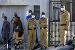 Private guards wear masks while standing outside a hospital, where victims of toxic gas leak are treated in Kamari neighborhood of Karachi, Pakistan, Monday, Feb. 17, 2020. A toxic gas leak killed five people and sickened dozens of others in a coastal residential area in Pakistan's port city of Karachi, police said Monday. The source of the leak, which occurred on Sunday night, and the type of gas that had leaked were not immediately known. There was no suspicion of sabotage. (AP Photo/Fareed Khan)