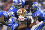 San Francisco 49ers running back Elijah Mitchell (25) is gang tackled by the Detroit Lions in the second half of an NFL football game in Detroit, Sunday, Sept. 12, 2021. (AP Photo/Lon Horwedel)