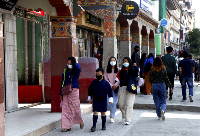 Bhutanese people wearing face masks as precaution against coronavirus walk through a street in Thimpu, Bhutan, Monday, April 12, 2021. The tiny Himalayan kingdom wedged between India and China has vaccinated nearly 93% of its adult population since March 27. Overall, the country has vaccinated 62% of its 800,000 people. (AP Photo)