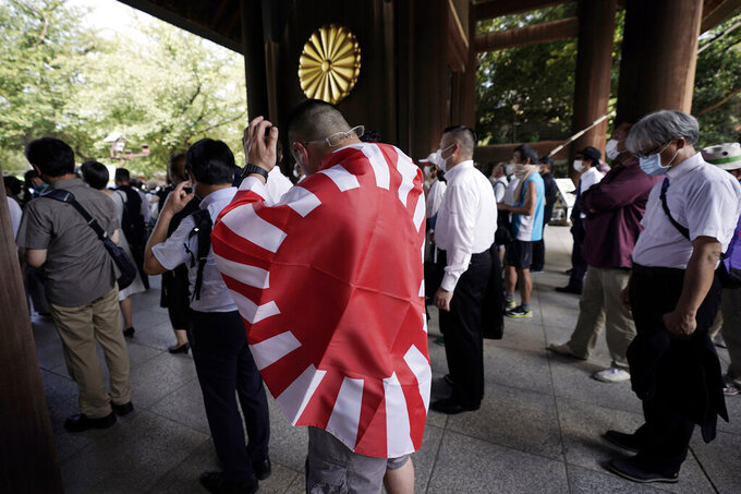 """FILE - In this Aug. 15, 2020, file photo, a visitor carrying a rising sun flag enters Yasukuni Shrine in Tokyo as Japan marked the 75th anniversary of the end of World War II. Japan's """"rising sun"""" flag is raising anger at the Olympics, with some of the host nation's neighbors calling for it to be banned during the Tokyo Games, which start Friday, July 23, 2021. (AP Photo/Eugene Hoshiko, File)"""