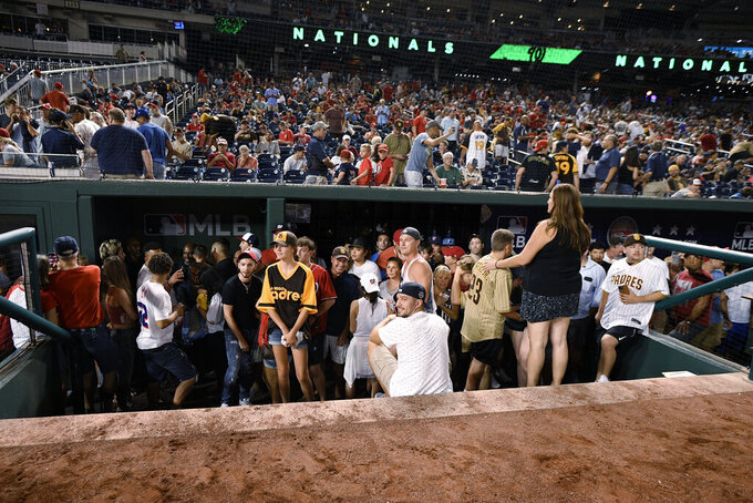 Spectators stand in the visiting team dugout during a stoppage in play due to an incident near the ballpark in the sixth inning of a baseball game between the Washington Nationals and the San Diego Padres, Saturday, July 17, 2021, in Washington. (AP Photo/Nick Wass)