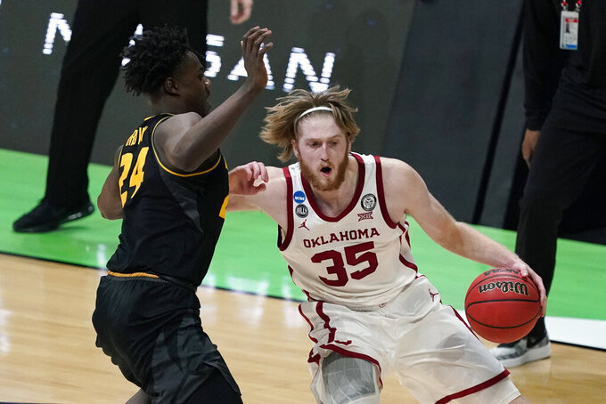 Oklahoma forward Brady Manek (35) drives past Missouri forward Kobe Brown, left, during the first half of a first-round game in the NCAA men's college basketball tournament at Lucas Oil Stadium, Saturday, March 20, 2021, in Indianapolis. (AP Photo/Darron Cummings)