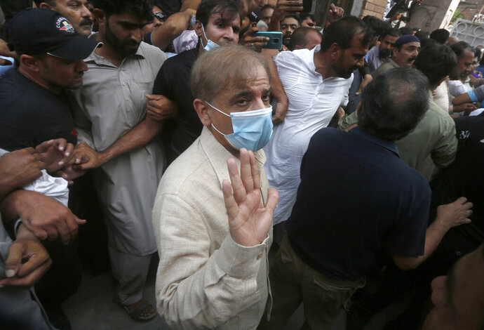 Pakistani opposition leader Shahbaz Sharif waves while being escorted by officials at Lahore High Court after his bail was rejected, in Lahore, Pakistan, Monday, Sept. 28, 2020. Pakistan's anti-graft body arrested Sharif Monday over his alleged involvement in a money laundering case after a court rejected bail for him, a move coming just before planned protests next month by his party seeking to force Prime Minister Imran Khan's resignation. (AP Photo/K.M. Chaudary)