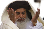 FILE - In this Nov. 24, 2017, file photo, the head of the Pakistani Tehreek-e-Labbaik radical religious party, Khadim Hussain Rizvi prays during a sit-in protest in Islamabad, Pakistan. A Pakistani court has sentenced 86 members of a radical Islamist party to 55-year prison terms each for taking part in violent rallies in 2018 over the acquittal of a Christian woman in a blasphemy case, a party official said Friday, Jan. 17, 2020. (AP Photo/B.K. Bangash, file)