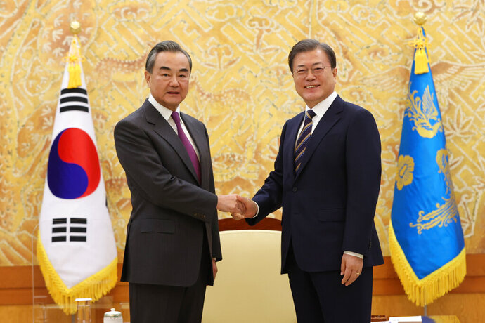 South Korean President Moon Jae-in, right, poses with Chinese Foreign Minister Wang Yi for a photo before a meeting at the presidential Blue House in Seoul, South Korea, Thursday, Nov. 26, 2020. (Kim Ju-sung/Yonhap via AP)