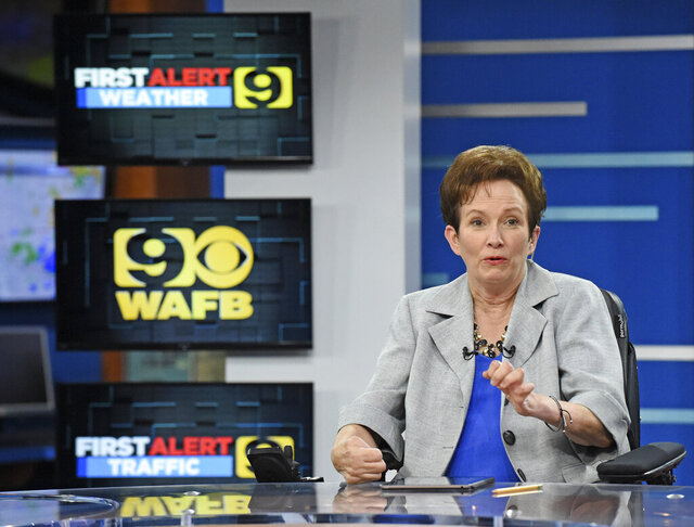 Longtime WAFB anchor Donna Britt waves as she sees her husband and son in the studio, Wednesday, June 13, 2018, as she signs off for one last time at WAFB studios in downtown Baton Rouge, La. Britt, who capped a nearly four-decade Louisiana broadcast journalism career with periodic on-air chronicles of her battle against a debilitating neurological disease, died Thursday, Jan. 21, 2021, in Baton Rouge. She was 62. (Hilary Scheinuk/The Advocate via AP)
