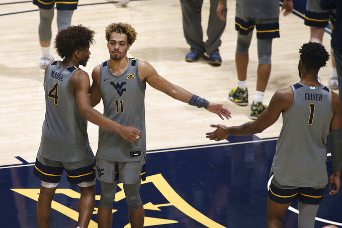 West Virginia guard Miles McBride (4), forward Emmitt Matthews Jr. (11) and Derek Culver (1) celebrate after a win over Kansas State during the second half of an NCAA college basketball game Saturday, Feb. 27, 2021, in Morgantown, W.Va. (AP Photo/Kathleen Batten)