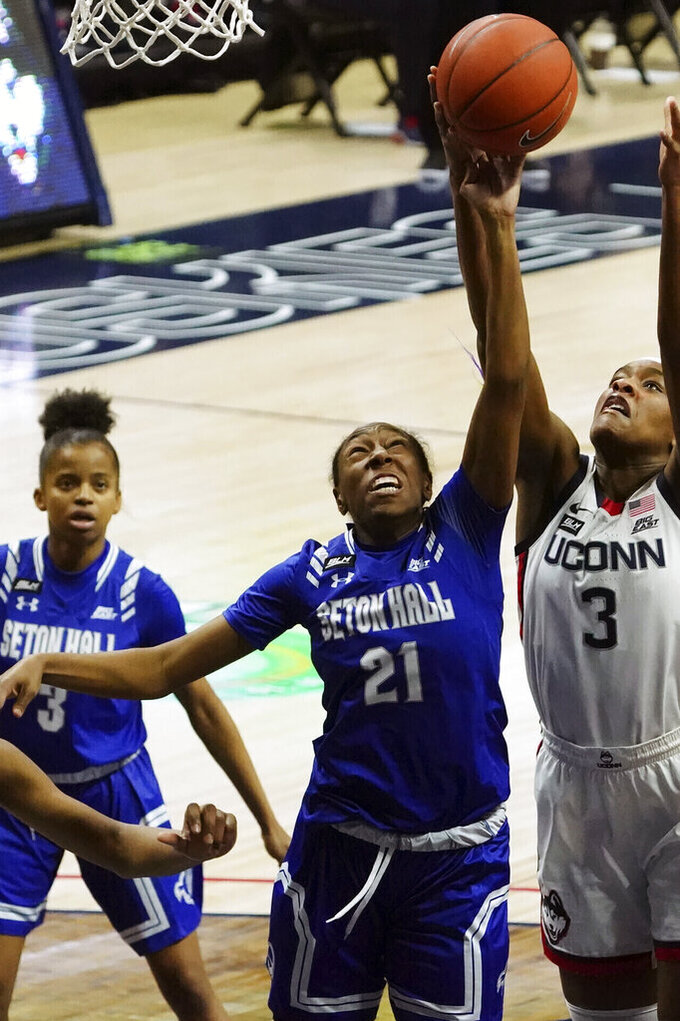 FILE - Connecticut forward Aaliyah Edwards (3) and Seton Hall guard Jasmine Smith (21) work for the rebound in the first half of an NCAA college basketball game in Storrs, Conn., in this Wednesday, Feb. 10, 2021, file photo. A former women's basketball player at Seton Hall University has been added to a lawsuit filed against the school by former men's player Myles Powell over what they claim were misdiagnosed knee injuries.  In an amended complaint to Powell's lawsuit filed Tuesday, Aug. 17, 2021, Jasmine Smith alleges team staff told her she'd suffered a bone bruise during practice in the fall of 2020. She alleged she was cleared to play and played the rest of the season despite suffering knee pain and swelling.  (David Butler II/Pool Photo via AP, FIle)
