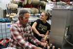 In this June 2, 2020, photo, Denali Brewing Co. founding partner Sassan Mossanen, left, and his daughter, Maya, cork bottles of coffee whiskey at Denali Brewing Co. in Talkeetna, Alaska. Talkeetna tourism businesses like the brewery and distillery, along with its main street brew pub, are feeling a financial squeeze after most major cruise ship companies have canceled their summer tourist seasons because of the coronavirus, meaning nearly half of Alaska's annual 2.2 million visitors won't be visiting Alaska. (AP Photo/Mark Thiessen)