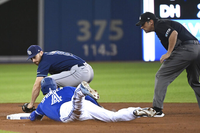 Toronto Blue Jays' George Springer (4) slides into second base with a double ahead of the tag by Tampa Bay Rays' Brandon Lowe during the fourth inning of a baseball game Tuesday, Sept. 14, 2021, in Toronto. (Jon Blacker/The Canadian Press via AP)