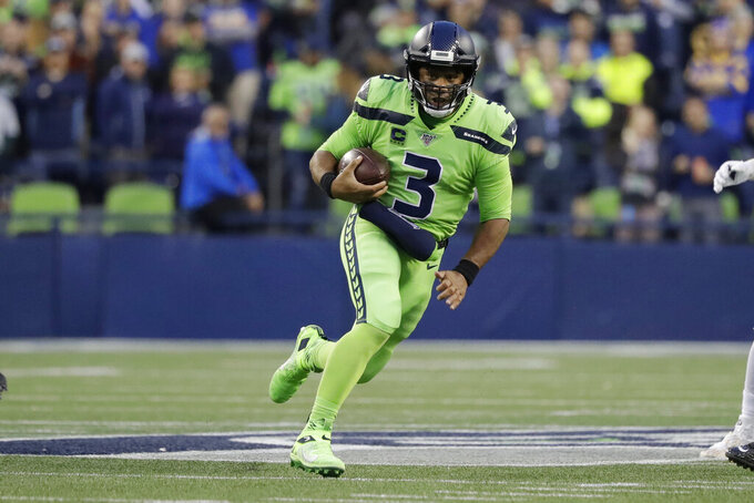 Seattle Seahawks quarterback Russell Wilson carries the ball during the first half of the team's NFL football game against the Los Angeles Rams on Thursday, Oct. 3, 2019, in Seattle. (AP Photo/Elaine Thompson)
