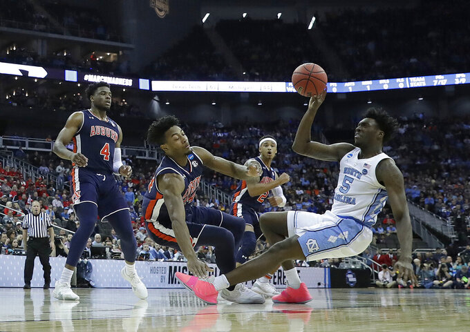 North Carolina's Nassir Little (5) tries to get off a shot as Auburn's Malik Dunbar (4), Anfernee McLemore and Bryce Brown (2) defend during the first half of a men's NCAA tournament college basketball Midwest Regional semifinal game Friday, March 29, 2019, in Kansas City, Mo. (AP Photo/Charlie Riedel)