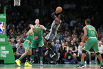 Brooklyn Nets guard Caris LeVert (22) shoots over Boston Celtics' Daniel Theis (27) and Carsen Edwards during overtime of an NBA basketball game Tuesday, March 3, 2020, in Boston. (AP Photo/Mary Schwalm)