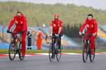 Ferrari driver Sebastian Vettel of Germany, center, cycles with other team members on the Istanbul Park circuit racetrack in Istanbul, Thursday, Nov. 12, 2020, ahead of the Formula One Turkish Grand Prix that will take place on Sunday. (AP Photo/Emre Oktay)