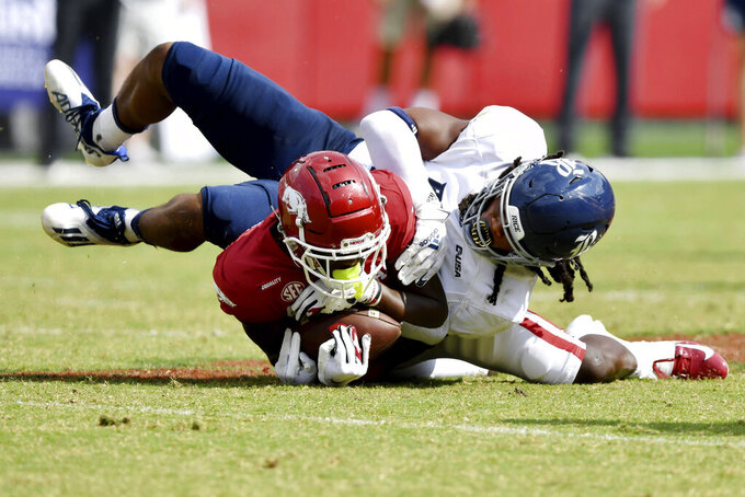 Arkansas receiver Ketron Jackson Jr. (2) is tackled by Rice defender Treshawn Chamberlain (17) during the second half of an NCAA college football game Saturday, Sept. 4, 2021, in Fayetteville, Ark. (AP Photo/Michael Woods)