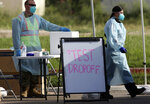 Health officials and members of the military assist during COVID-19 testing, Wednesday, July 8, 2020, at HEB Park in Edinburg, Texas. (Delcia Lopez/The Monitor via AP)